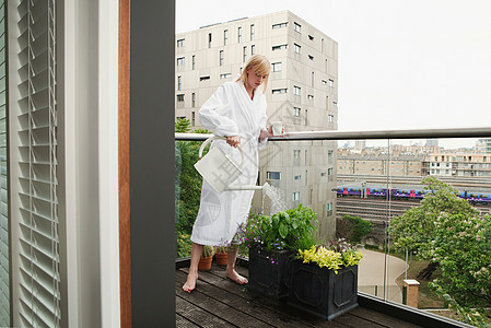 在阳台上浇花的女人图片