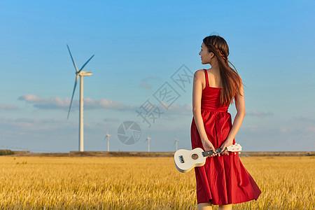 年轻美女手拿尤克里里背影图片