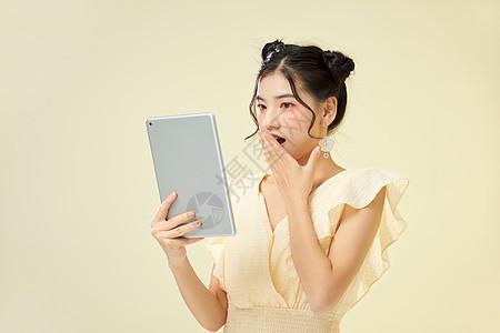可爱女性手捧平板电脑惊讶图片