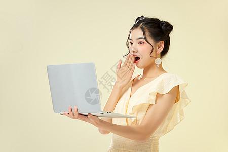 可爱女性手捧笔记本电脑惊讶图片