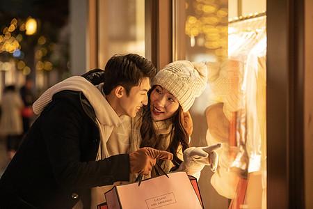冬季情侣购物橱窗前挑选衣服图片