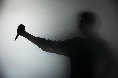 左手持刀的男性剪影图片