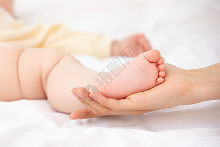 妈妈用手托着宝宝的脚图片