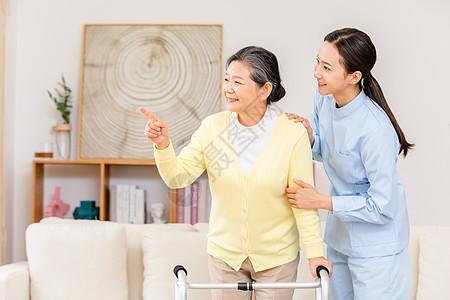 护工扶着使用健步器的老奶奶锻炼身体图片