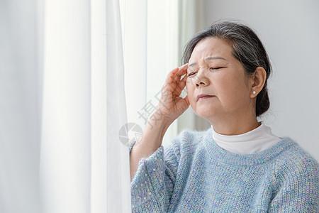 靠在窗边头疼的女人图片
