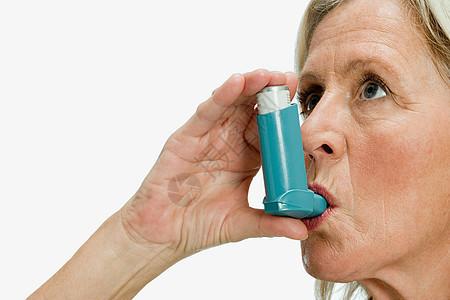 使用哮喘吸入器的妇女图片