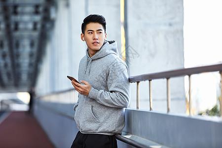 年轻运动男生使用蓝牙耳机通电话图片