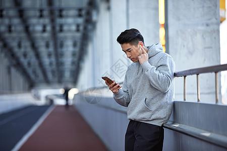 年轻运动男士户外使用蓝牙耳机通电话图片