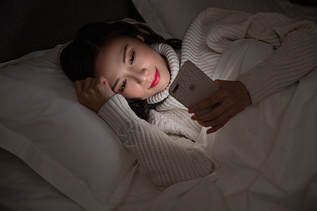 青年女性夜晚熬夜玩手机图片