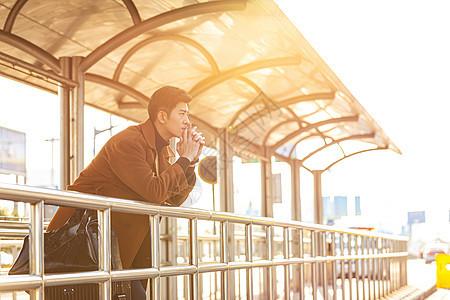 夕阳下青年男性车站等待公交站图片