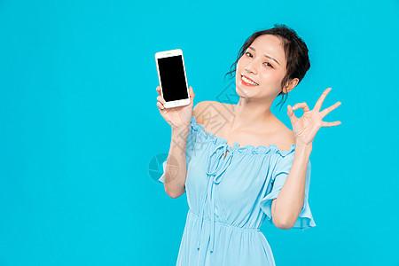 青年美女拿手机展示图片