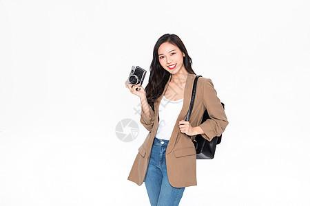 青年美女旅行出游拿相机拍照图片