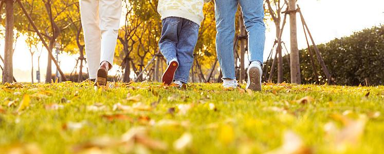 爸爸妈妈带着女儿在公园草地奔跑图片