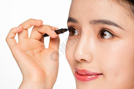 美女拿眼线笔化妆画眼线图片