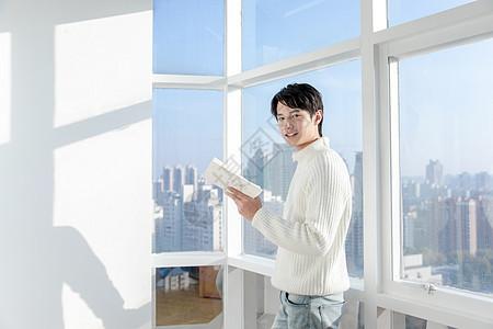 居家男性坐在阳台上看书图片