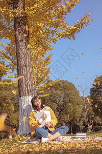 倚靠在银杏树下看书的女孩图片