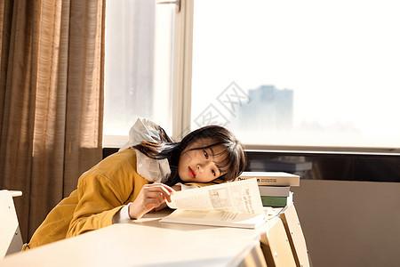 趴在课桌上看书的女大学生图片