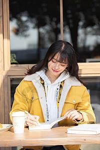 坐在咖啡厅学习的女大学生图片