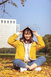 坐在铺满银杏叶的草坪上看书的女孩 图片