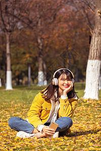 坐在铺满银杏叶的草坪上听音乐的女孩图片