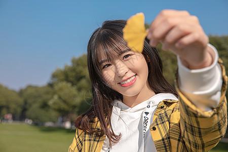 手拿银杏叶的女孩图片