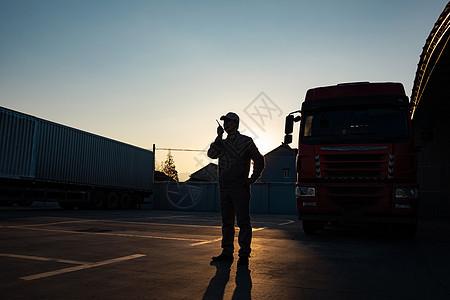 货车司机手拿对讲机逆光剪影形象图片