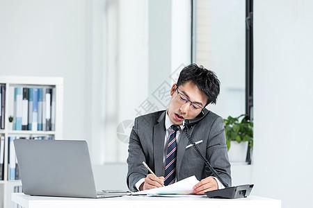 商务男性一边打电话一边工作图片