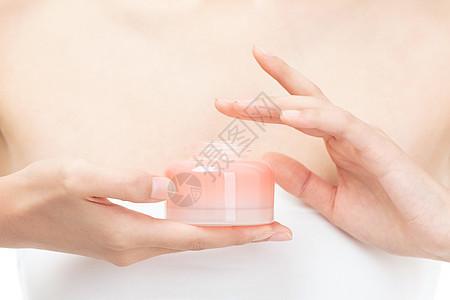 手拿护肤品的女性特写图片