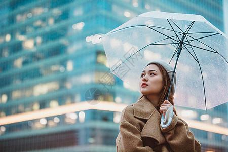 冬季女性户外下雨天撑伞看远方图片