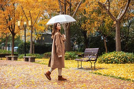 秋季雨天美女撑伞公园散步图片