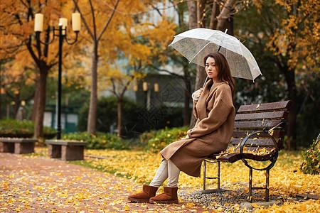秋季雨天美女公园撑伞图片