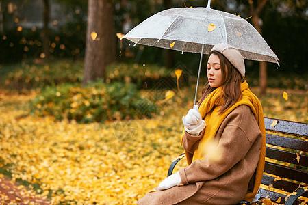 秋季银杏树下悲伤美女撑伞图片
