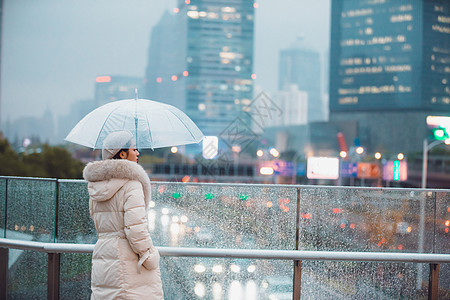 冬季户外孤单女性背影撑伞图片