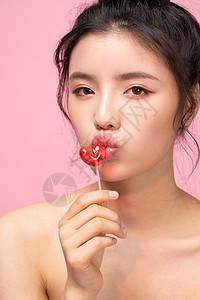 年轻女孩吃心形棒棒糖特写图片