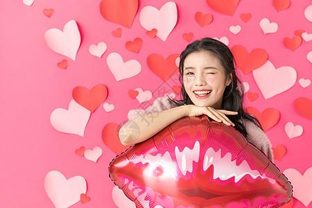 捧着红唇气球的甜美女性图片