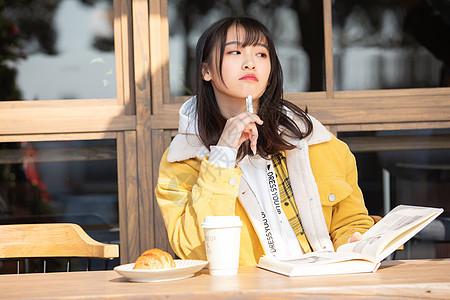 坐在咖啡馆思考的女大学生图片