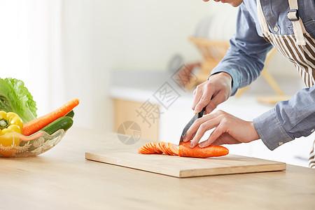 年轻男士在厨房切菜特写图片