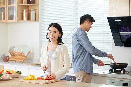 年轻夫妻在厨房一起做菜图片