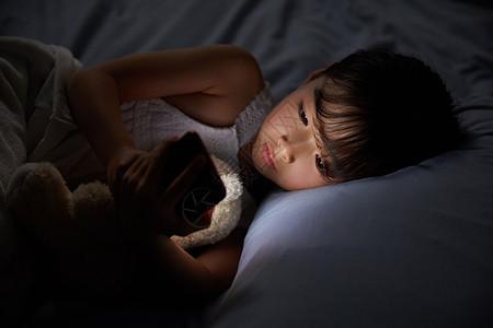 小女孩躺在床上玩手机图片