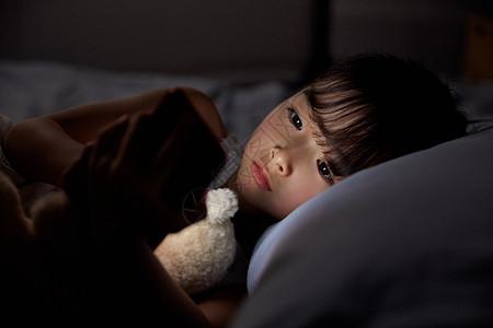 小女孩夜晚躺床上玩手机图片