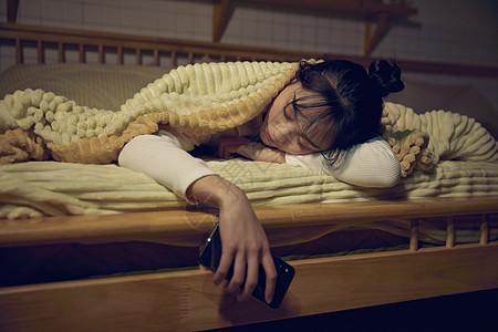 年轻女性在家熬夜玩手机睡着图片