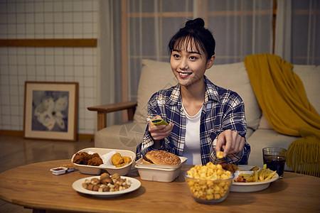 年轻美女在家吃夜宵看电视图片