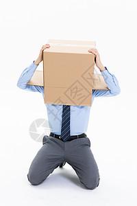 跪在地上头上套纸盒箱的绝望商务男性图片