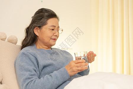 老年人躺床上喝水吃药图片