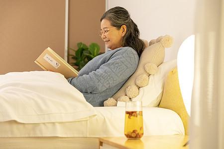 老奶奶睡前看书喝养生茶图片