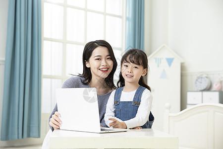 妈妈陪着女儿用笔记本电脑上网课图片