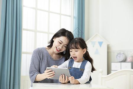 妈妈陪伴女儿平板电脑在家上课图片