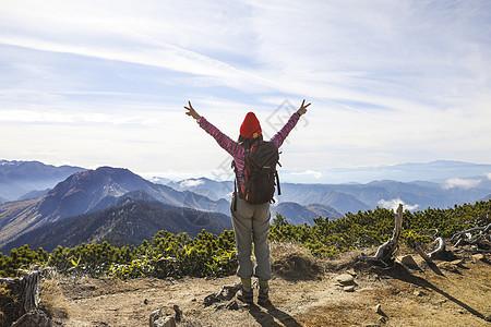 在山顶张开双臂的女人背影图片
