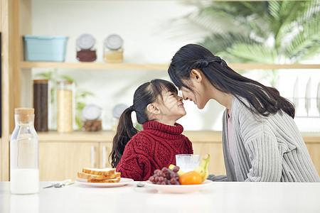 年轻妈妈和女儿吃早餐互动图片