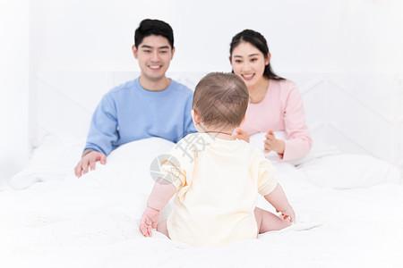 爸爸妈妈带着婴儿在床上玩耍图片